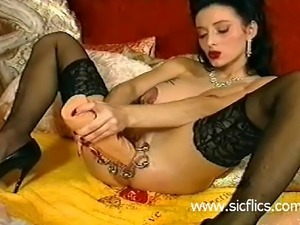 Busty bizarre brunette babe fucks a gigantic dildo in her huge heavily...