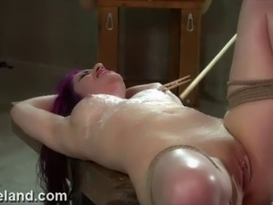 Redhead submissive chained to a rack and sexually tormented by FemDom