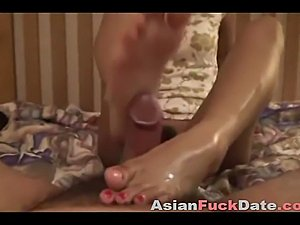 Pretty Asian girl giving oily footjob tits her sexy toes