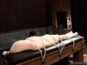 Brunette domme in read leather tortures a bound and wrapped slave