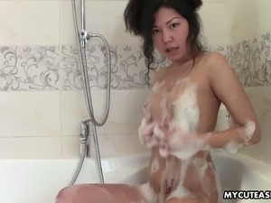 Playful Japanese gal strokes foamy body in the bath room