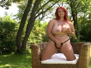 busty redhead whith big  boobs strips naked in a pool