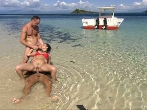 Babe is enjoying two men's attention on the beach