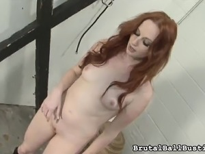 Helpless guy has a provoking redhead in black boots biting his shaft