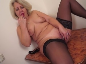 Horny mature blonde with fake tits fingering her juicy pussy