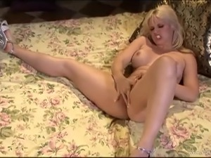 Curvy blonde with fake tits moaning while fingering her pussy
