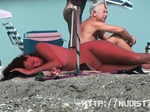 Short haired sweetie filmed on a nudist beach