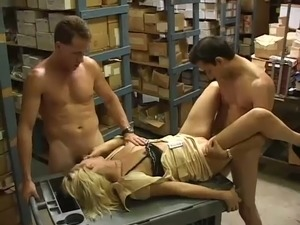 Perverted secretary Violet DeVoe is fucked by studs in the warehouse
