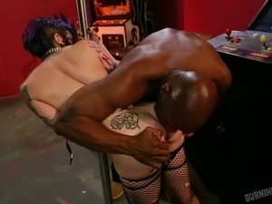Tattooed pole dancer gives good blowjob to horny black dude